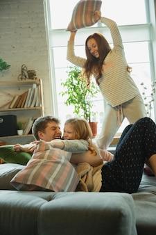 家族は家で一緒に素敵な時間を過ごし、幸せで陽気に見え、枕と戦っています