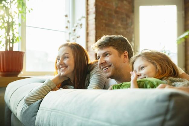 Семья приятно проводит время вместе дома, выглядит счастливой и веселой, лежа вместе