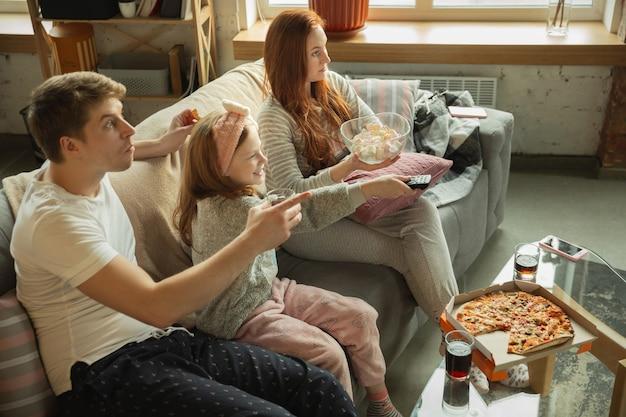 家で一緒に素敵な時間を過ごす家族は、幸せで陽気に見えます。ママ、パパ、娘が楽しんで、ピザを食べて、スポーツの試合やテレビを見ています。一体感、家の快適さ、愛、関係の概念。