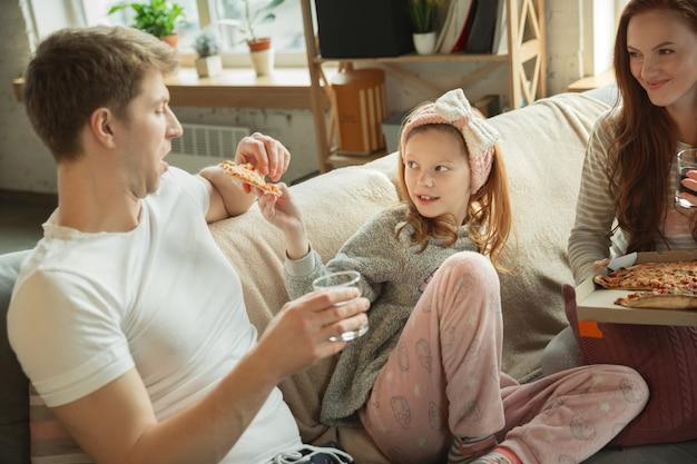 家で一緒に素敵な時間を過ごす家族は幸せで陽気なお母さんお父さんと娘に見えます