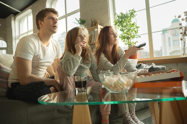 家族は家で一緒に素敵な時間を過ごし、幸せで興奮しているように見え、ピザを食べ、スポーツの試合を見ています