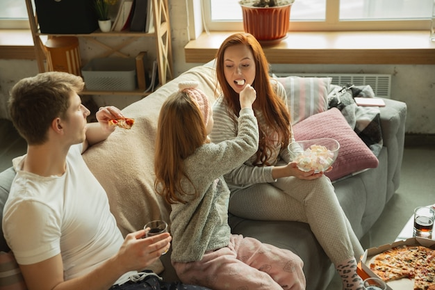 Family spending nice time together at home, looks happy and cheerful, eating pizza