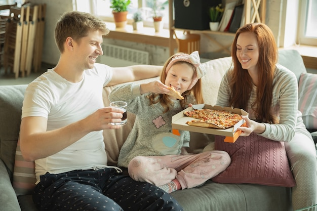 Family spending nice time together at home looks happy and cheerful eating pizza