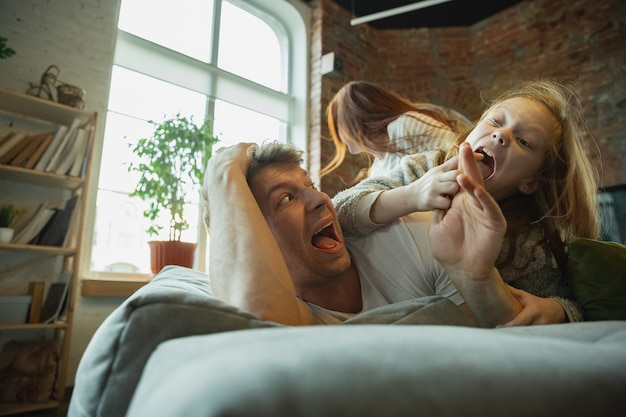 Family spending nice time together at home, looks happy and cheerful, lying down together