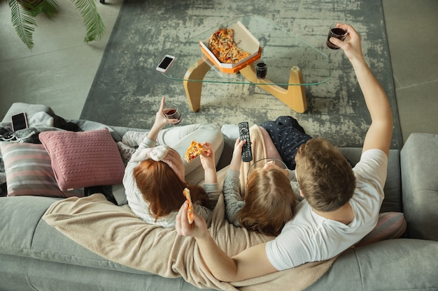 Family spending nice time together at home, looks happy and cheerful. mom, dad and daughter having fun, eating pizza, watching sport match or tv. togetherness, home comfort, love, relations concept.
