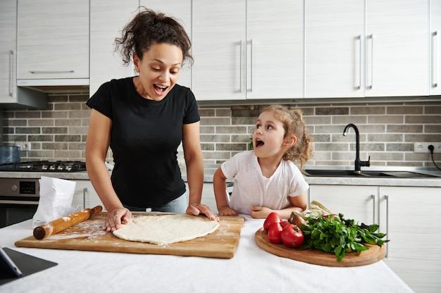 家族の過ごす時間の概念。子供たちに料理の仕方を教える。幸せな母と娘が丸い形のピザ生地を作り、家で一緒に料理します。