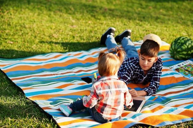 一緒に時間を過ごす家族。ピクニック毛布で屋外の絵を描く姉妹と兄弟。