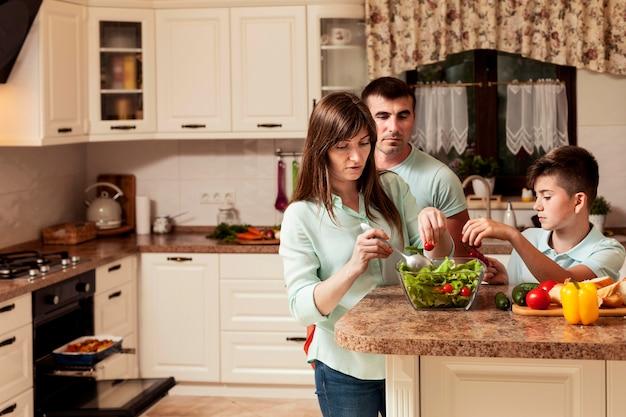 食糧を準備するキッチンで一緒に時間を過ごす家族