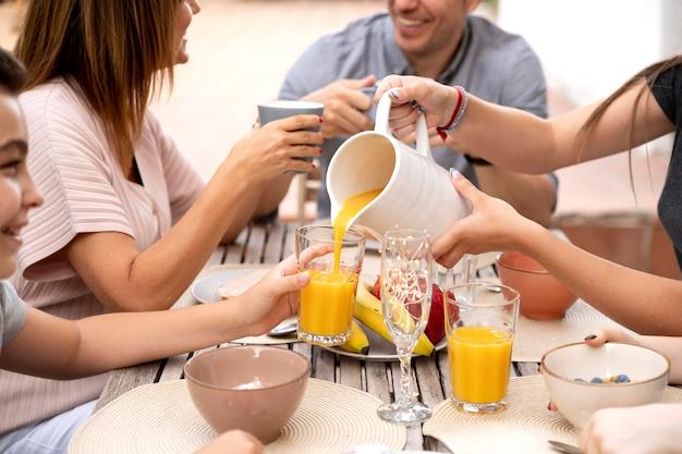 屋外で一緒に時間を過ごし、オレンジジュースを飲む家族