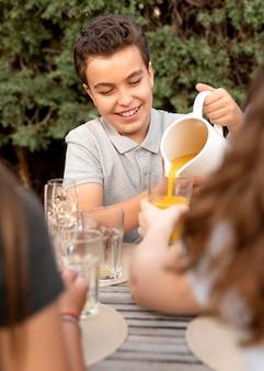La famiglia trascorre del tempo insieme all'aperto e beve succo d'arancia