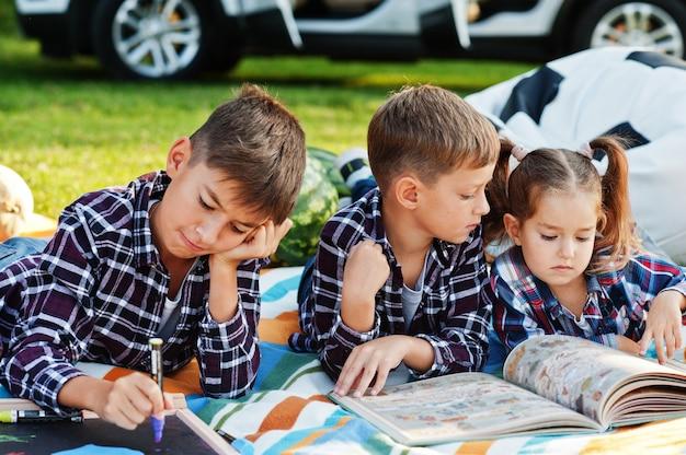 함께 시간을 보내는 가족. 피크닉 담요에 야외 세 아이입니다.