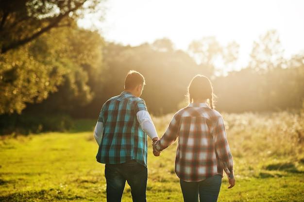 一緒に時間を過ごす家族。日没時に市松模様のシャツを着た妻と夫。