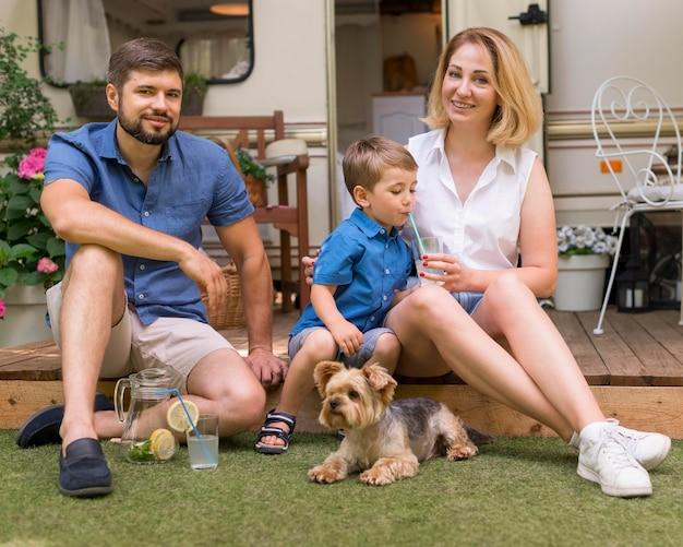 Семья проводит время вместе со своей собакой на улице