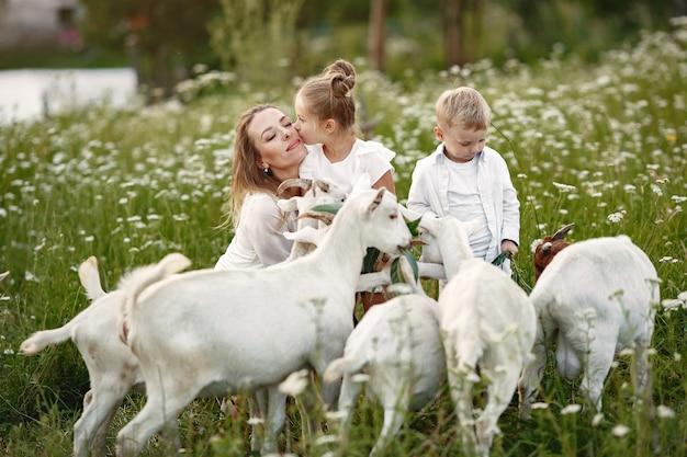 La famiglia trascorre il tempo in vacanza nel villaggio. ragazzo e ragazza che giocano in natura. le persone camminano all'aria aperta.