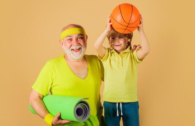 Семейный спорт. дедушка с циновкой для йоги и ребенок с баскетбольным мячом. дедушка и внук занимаются спортом.
