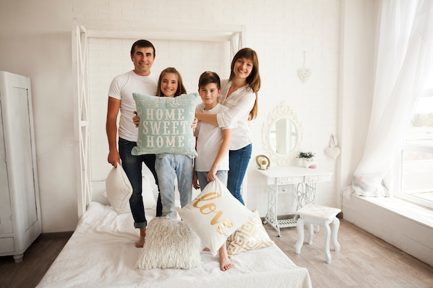 Family standing on bed with holding home sweet home text on pillow