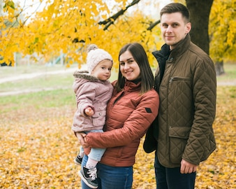 Family standing in autumn park