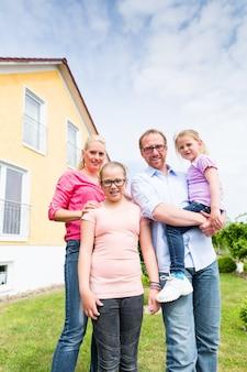 집이나 집 앞에 서있는 가족