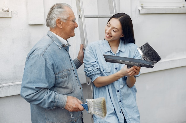 Family standing near building with repair tools
