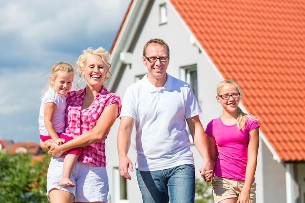 Family standing proud in front of home