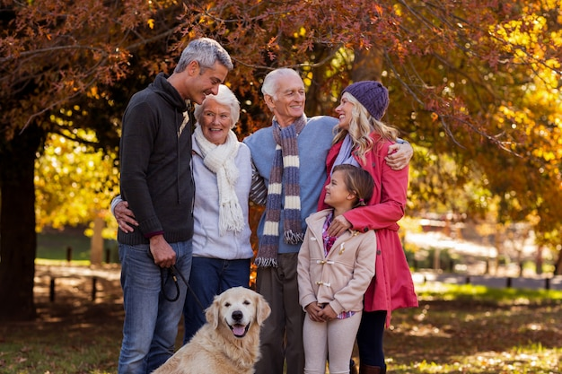 Family standing with dog at park
