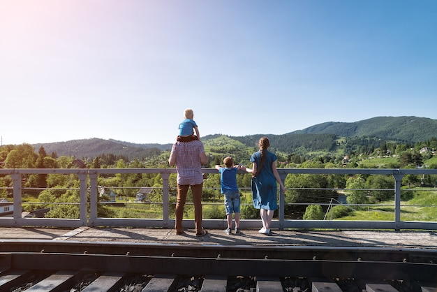Family stands on the platform on nature background. waiting for the train. travel with family.