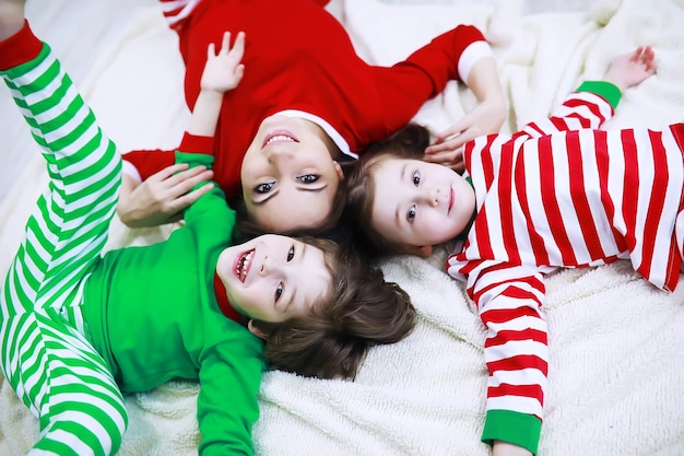 A family in striped pajamas is resting at home. little children dressed as elves are lying on the sofa. a happy family.