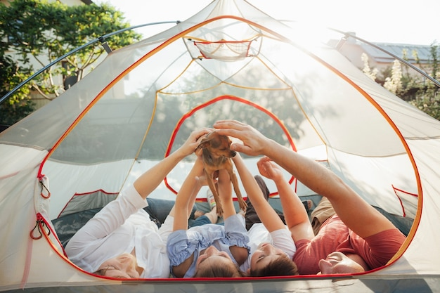Family stroking little dog while lying in tent