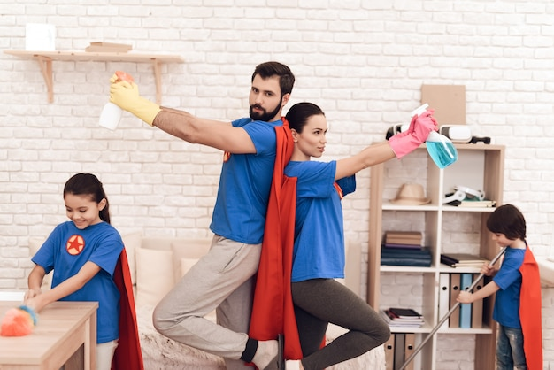 Family in suits of superheroes poses on the camera at home.