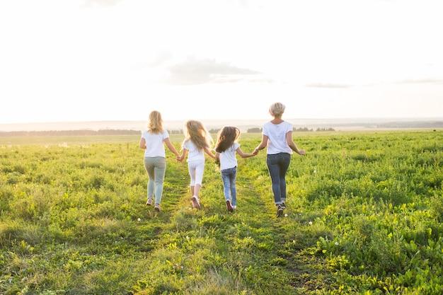 가족, 여름, 휴가 개념-그린 필드에서 멀리가는 여자와 여자의 그룹