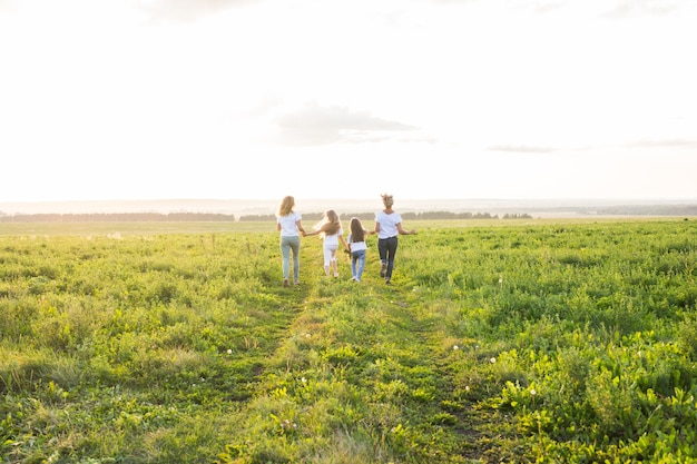 Концепция семьи, лета и отдыха - группа женщин и девочек, уходящих в зеленое поле