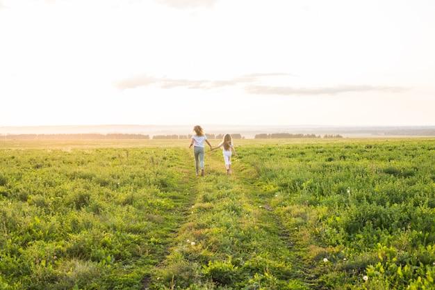 Концепция семьи, лета и отдыха - мать держит руку дочери в зеленом поле