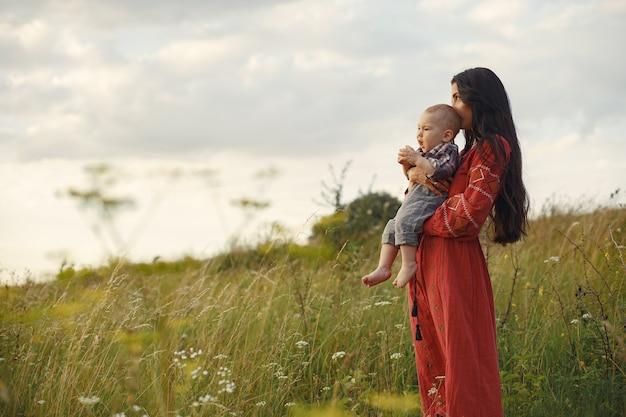 Famiglia in un campo estivo. madre in un vestito rosso. ragazzino sveglio.