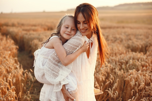 Family in a summer field. sensual photo. cute little girl. woman in a white dress.