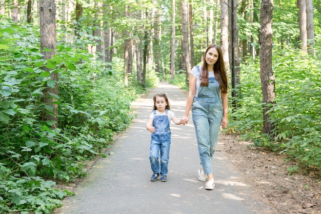 Family, summer and nature concept - attractive young woman and beautiful little daughter girl
