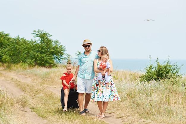 Семья, летние каникулы, усыновление и люди концепции - счастливый мужчина, женщина и дочери в темных очках, с чемоданами веселились над голубым небом