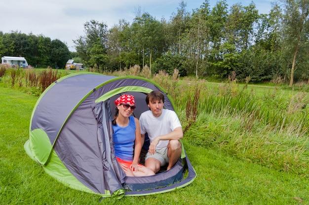 キャンプでの家族の夏休み。テントの中で幸せな笑みを浮かべてアクティブなカップル。