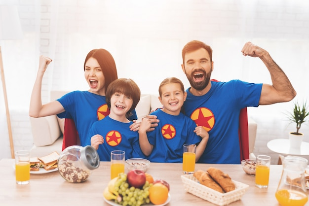 A family of superheroes sit at a table.