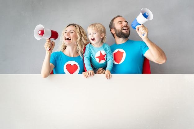 Family of superheroes speaking to megaphone