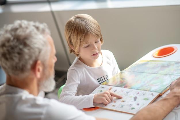 家族のサポート。父親と一緒に面白い本を読んでいる少年