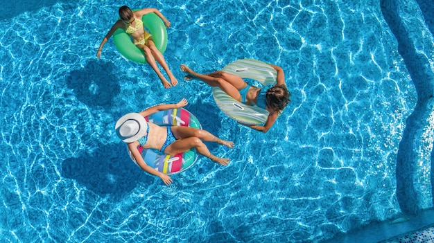 Family in swimming pool aerial drone view from above, happy mother and kids swim on inflatable ring donuts and have fun in water on family vacation