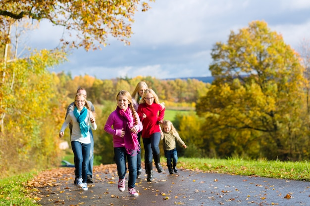 Family take a walk in autumn forest