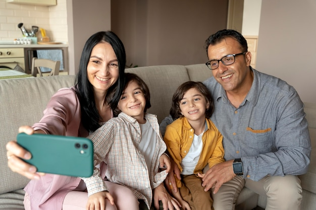 Семья, делающая селфи со смартфоном
