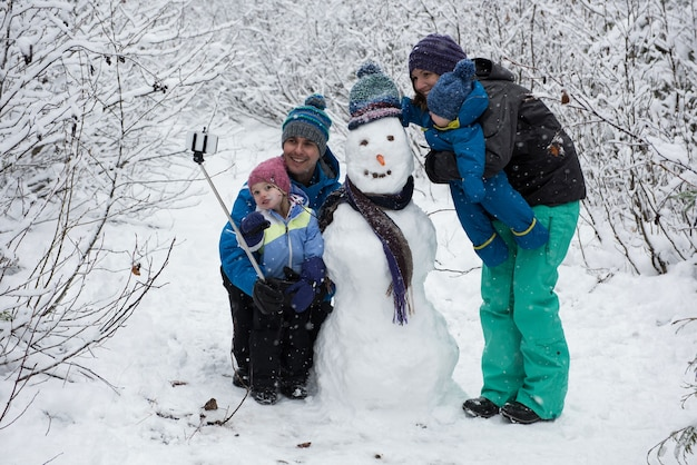 Family taking selfie with snowman