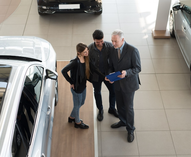 Family talking to the salesman and choosing their new car in a showroom