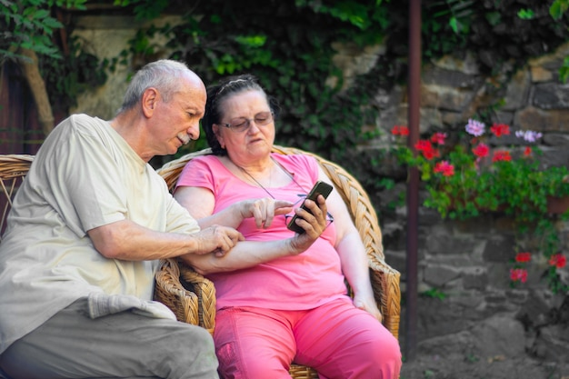 Family and technology concept. senior couple using smartphone outdoors in the garden