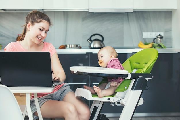 Семья мать кормит ребенка на кухне, счастливы вместе дома, улыбаясь на кухне