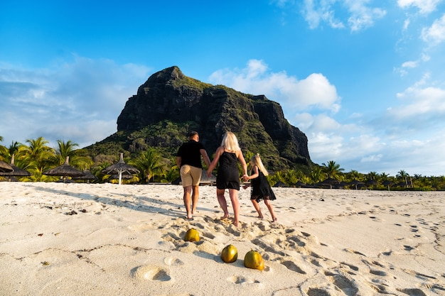 A family of three in black clothes on the white beach of le morne on the island of mauritius.