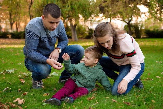 Family of three enjoy autumn park having fun smile
