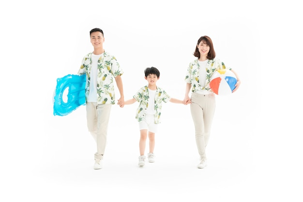 Family of three holding beach ball and surfboard